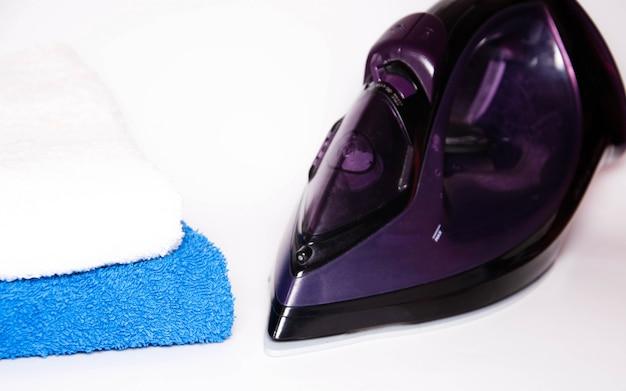Modern ijzer op een witte achtergrond met blauwe en witte handdoeken. uitzicht vanaf de bovenkant, zijkant. macro. ijzer en gestreken dingen. plaats voor tekst