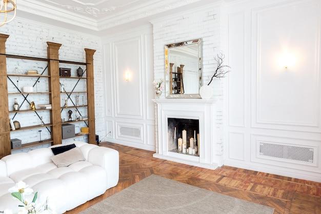Modern interieur van een luxe grote lichte woonkamer. witte dure bank en houten planken, witte muren met lijstwerk en een luxe kroonluchter