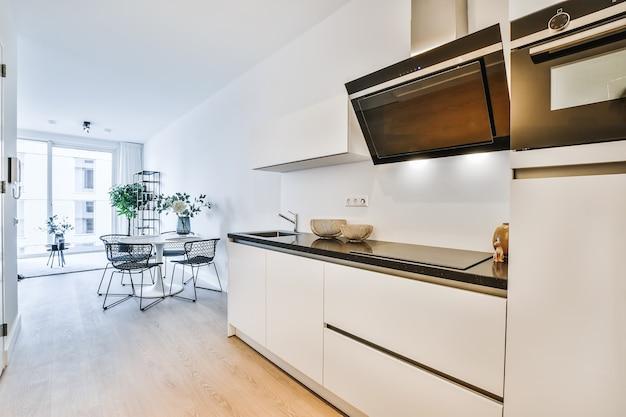 Modern interieur van kleine huiskeuken van ongebruikelijke geometrische vorm met meubels en toestellen in witte en zwarte tinten