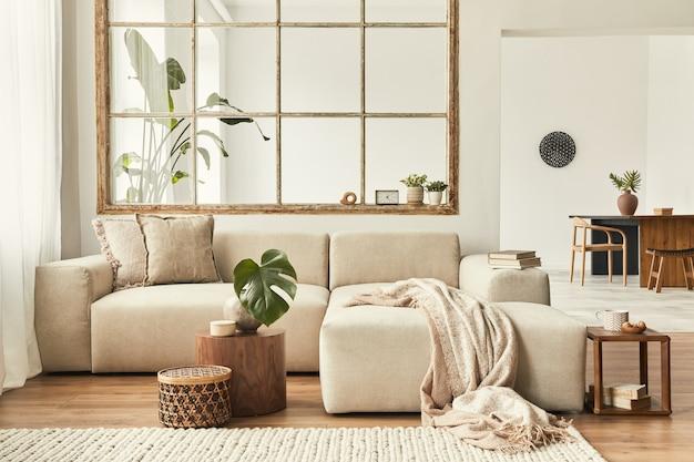 Modern interieur van open ruimte met design modulaire bank, meubels, houten salontafels, plaid, kussens, tropische planten en elegante persoonlijke accessoires in stijlvol interieur. neutrale woonkamer.
