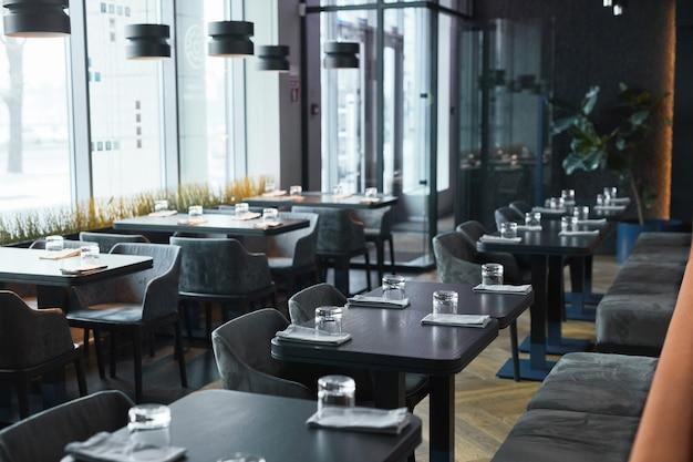 Modern interieur van restaurant in grijze kleur ingerichte zachte stoelen en zwarte tafels met glazen en servetten