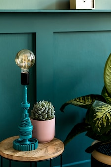Modern interieur van slaapkamer met design salontafel, tafellamp, sappige en mooie plant. groene wandbekleding. stijlvolle huisstaging. . detailopname.