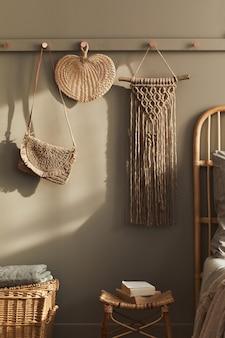 Modern interieur van stijlvolle slaapkamer met decoratie, neutraal macramé, kleerhanger, gedroogde bloem, mand, mooie lakens, deken, kussens en persoonlijke accessoires