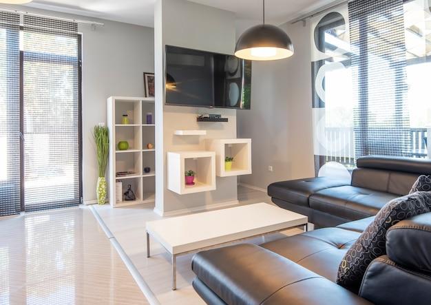 Modern interieur van woonkamer met comfortabele zwarte leren bank