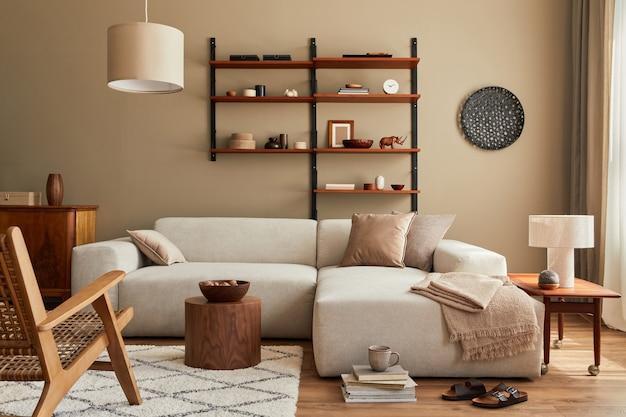 Modern interieur van woonkamer met design modulaire beige bank, salontafel, meubels, hanglamp, plank, pantoffels, tapijt, decoratie en elegante persoonlijke accessoires in woondecoratie..