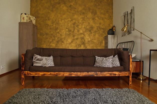 Modern interieur van woonkamer met getextureerde gouden muur, bruine houten stijlvolle bank en meubelen