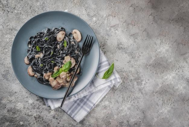 Modern italiaans diner, mediterraan eten, zwarte inktvis spaghetti pasta met champignon champignons