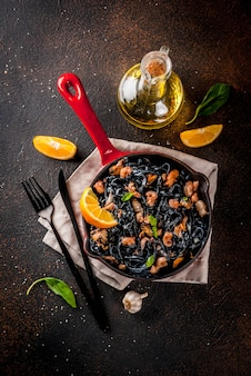 Modern italiaans diner, mediterraan eten, zwarte inktvis spaghetti pasta met zeevruchten
