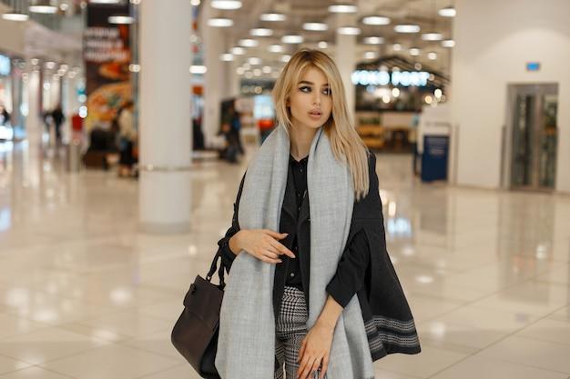 Modern jong blond vrouwenmodel in een chique modieuze jas