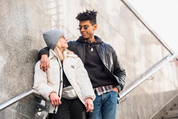Modern jong paar die tussen verschillende rassen zonnebril dragen die zich op trap bevinden die elkaar bekijken