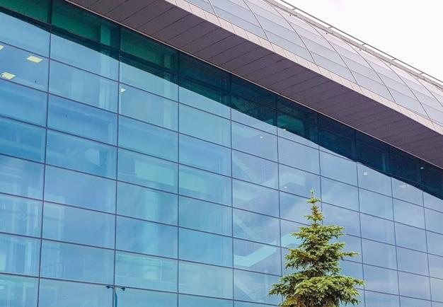 Modern kantoor commercieel gebouw gemaakt van glas en beton, buitenaanzicht, sparren op de achtergrond van het gebouw.