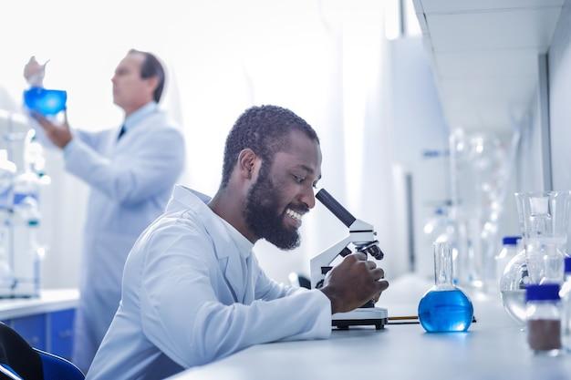 Modern laboratorium. gelukkig slimme aardige wetenschapper die in het laboratorium zit en tijdens het doen van een onderzoek werkt