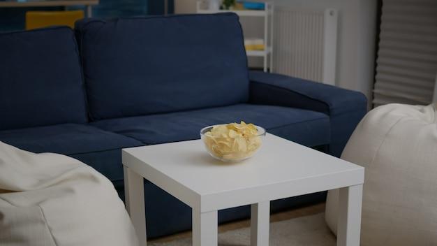 Modern leeg appartement met niemand erin is klaar voor een nachtfeest met een chipskom op een houten tafel. de woonkamer is voorbereid op het verzamelen van vrienden die 's avonds laat een verjaardagsfeestje vieren