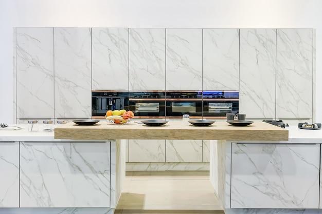 Modern, licht, schoon keukeninterieur met roestvrijstalen apparaten in een luxe appartement.