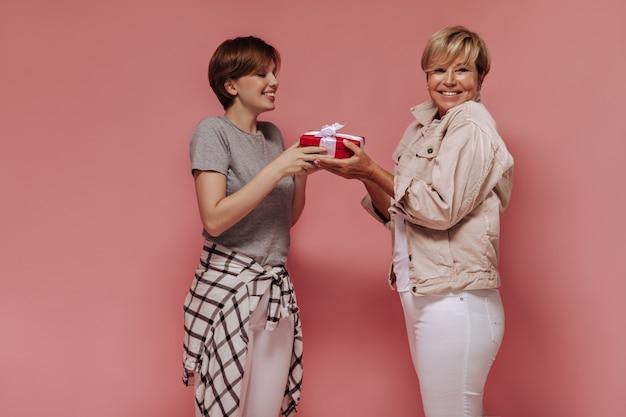 Modern meisje met kort kapsel in koele kleding rode geschenkdoos geven blonde dame in beige jas en lichte broek op roze achtergrond.