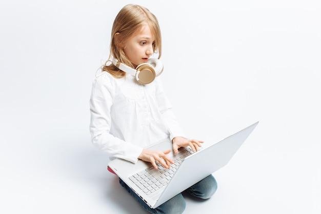 Modern meisje zitten met laptop en luisteren naar muziek, schattig en mooi