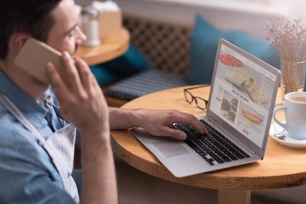 Modern menu. drukke jonge knappe man met behulp van laptop en een gesprek op mobiel zittend aan tafel.