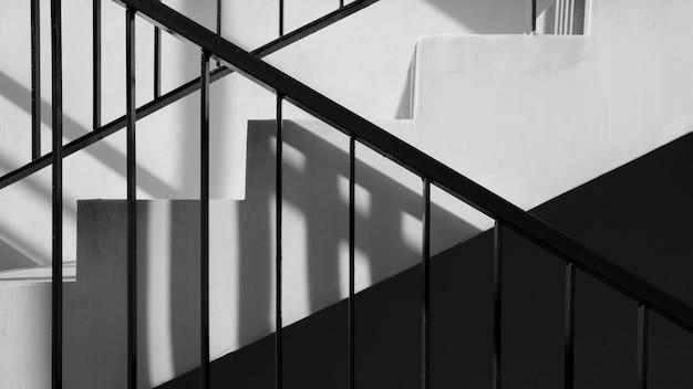 Modern metaaltraliewerk bij trap met schaduw in een modern concreet gebouw