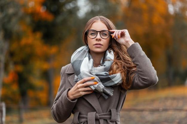 Modern modieus jong vrouwenmodel met stijlvol kapsel maakt trendy bril recht. mooie hipster meisje in stijlvolle seizoensgebonden warme kleding in een vintage sjaal poseren buiten in de herfst bos.