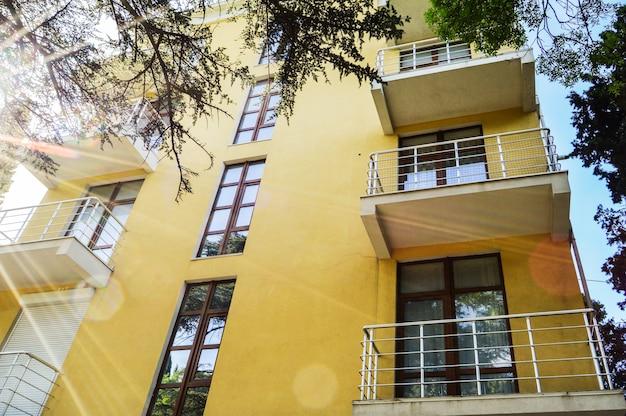 Modern mooi luxe geel resortgebouw met balkons, zonnige zomerdag.