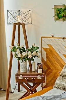 Modern nachtkastje in slaapkamer slaapkamer in loftstijl met vaas en bloemen en lamp op grote houten poten