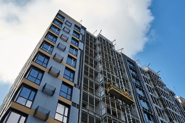 Modern nieuw gebouw in aanbouw tegen blauwe hemel