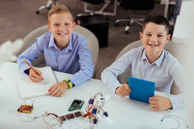 Modern onderwijs. blije positieve jongens die glimlachen terwijl ze genieten van hun les