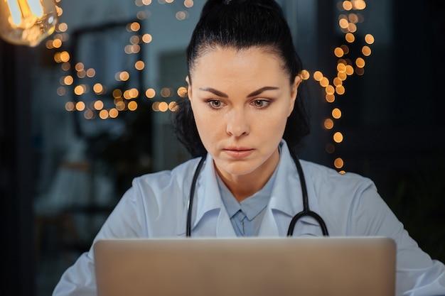 Modern onderzoek. ernstige aardige aantrekkelijke vrouw die naar het laptopscherm kijkt en zich op haar taak concentreert terwijl zij wetenschappelijk onderzoek doet