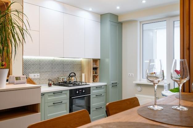 Modern oranje wit en blauwgroen keukenbinnenland met eethoek