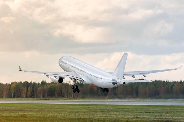 Modern passagiersvliegtuig met brede romp vliegt over de startbaan van de luchthaven