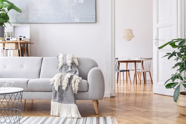 Modern scandinavisch woonkamerinterieur met designbank, elegante deken, salontafel, boekenstandaard, planten en bruin houten parket