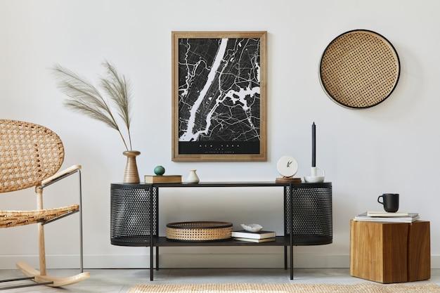 Modern scandinavisch woonkamerinterieur met frame, design commode, blad in vaas, rotan fauteuil, boek en elegante accessoires in stijlvol interieur..