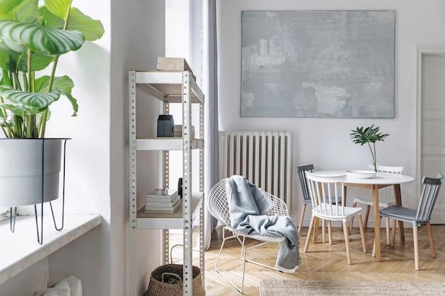 Modern scandinavisch woonkamerinterieur met grijze designbank, salontafel, planten, stijlvolle accessoires, decoratie, tapijt en boekenstandaards in een elegant interieur