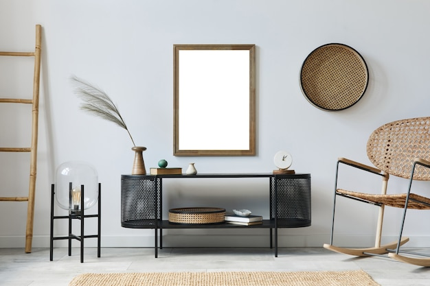 Modern scandinavisch woonkamerinterieur met mock-up posterframe, designcommode, blad in vaas, rotanfauteuil, boek en elegante accessoires in stijlvol interieur. sjabloon.