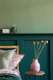 Modern slaapkamerinterieur met design salontafel, bloemen in vaas en elegante persoonlijke accessoires. mooie lakens, deken en kussens. . stijlvolle huisstaging. wandbekleding. details