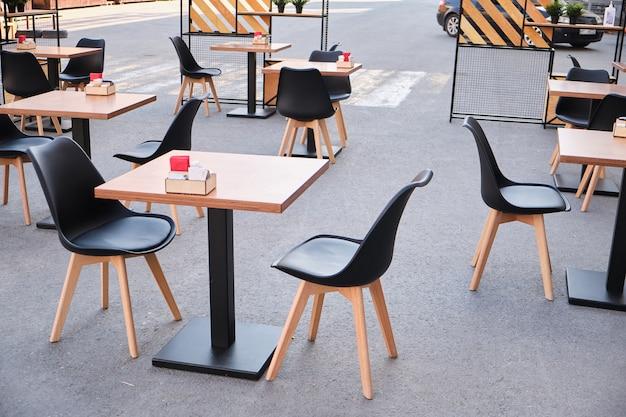 Modern stijlvol interieur van een straat café of restaurant. lege buitentafels en stoelen op straat
