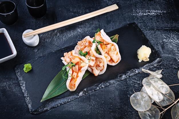 Modern tartaar van coquille met avocado in rijstchips. gezond eten. rauwe zeevruchten. rauwe coquille met microgroen en tobiko kaviaar. lekker eten geserveerd op een donkere achtergrond. japans eten stijl