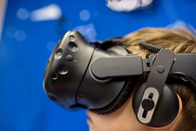 Modern technologie, gokken en mensenconcept - jongen in virtuele werkelijkheidshoofdtelefoon of 3d glazen die videospelletje spelen bij spelcentrum