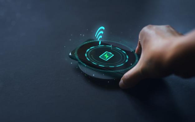 Modern technologisch concept hand die de telefoon verbindt met het draadloze oplaadapparaat
