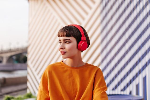 Modern tienermeisje met donkerbruin haar in oranje kleren op gestreepte muur