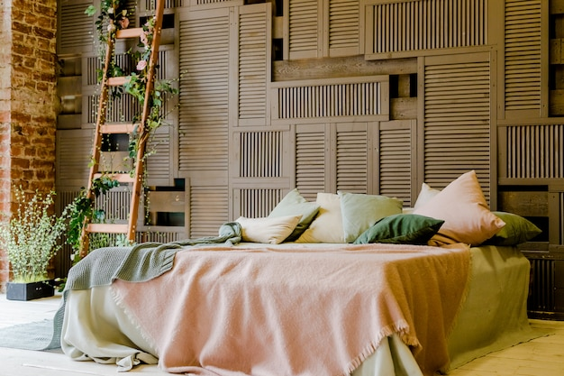 Modern tweepersoonsbed dat tegen een houten muur staat. interieur met groene en roze gezellige kussens. stijlvolle slaapkamer met een gezellig kingsize bed. loftstijl
