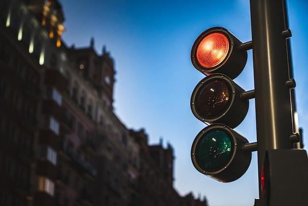 Modern verkeerslicht dat rode kleur bij nacht in een moderne stad toont