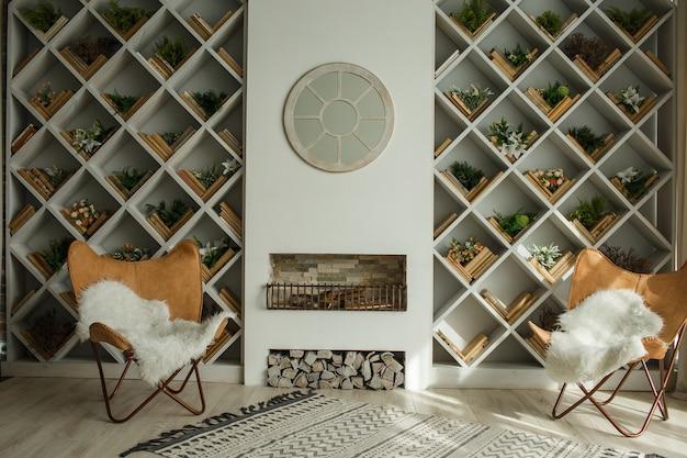 Modern voorjaarsinterieur met ingebouwde boekenkast, open haard en leren stoelen en ronde spiegel. luxe woonkamer en interieur