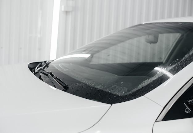 Modern wassen met schuim en hogedrukwater van een witte auto. carwash.