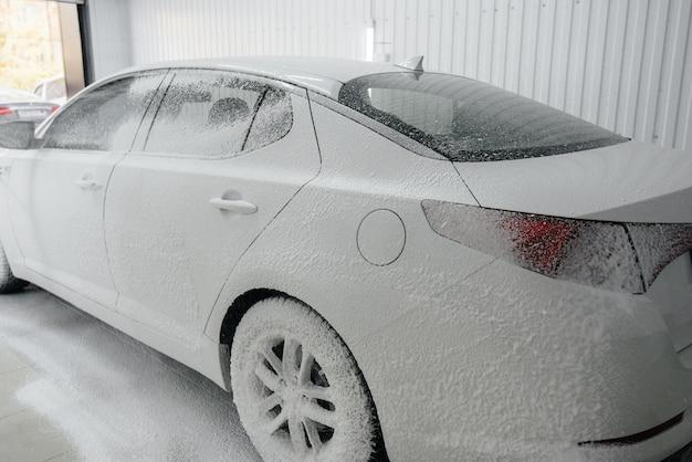 Modern wassen met schuim en water onder hoge druk van een witte auto. carwash.
