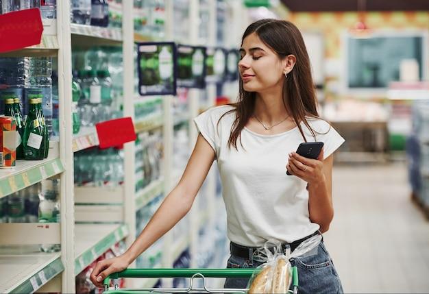 Modern winkelcentrum. vrouwelijke shopper in vrijetijdskleding in de markt op zoek naar producten.
