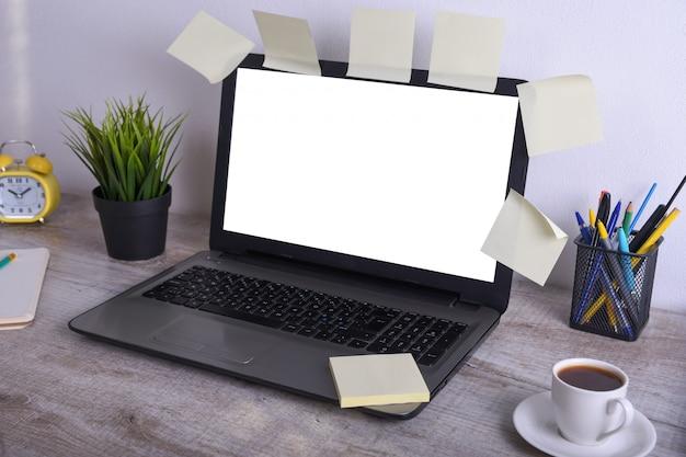 Modern wit bureau tafelmodel, werkruimte met laptopcomputer met wit scherm voor u tekst of afbeelding, groen gras, kopje koffie en een stapel papieren op witte rotsachtergrond.