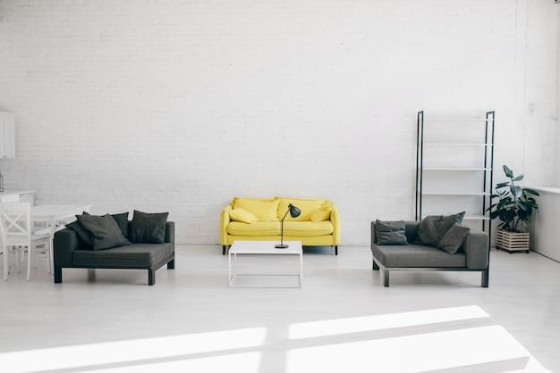 Modern woonkamerbinnenland in witte, zwarte en gele tinten. gezellige rustruimte met bank, salontafel en lege plank, comfortabel huisontwerp