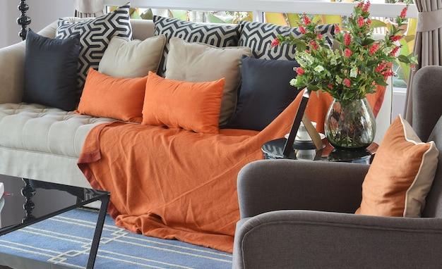 Modern woonkamerontwerp met bruine en oranje tweedbank en zwarte hoofdkussens