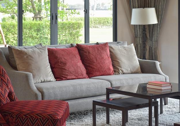 Modern woonkamerontwerp met rode hoofdkussens op bank en decoratieve schemerlamp